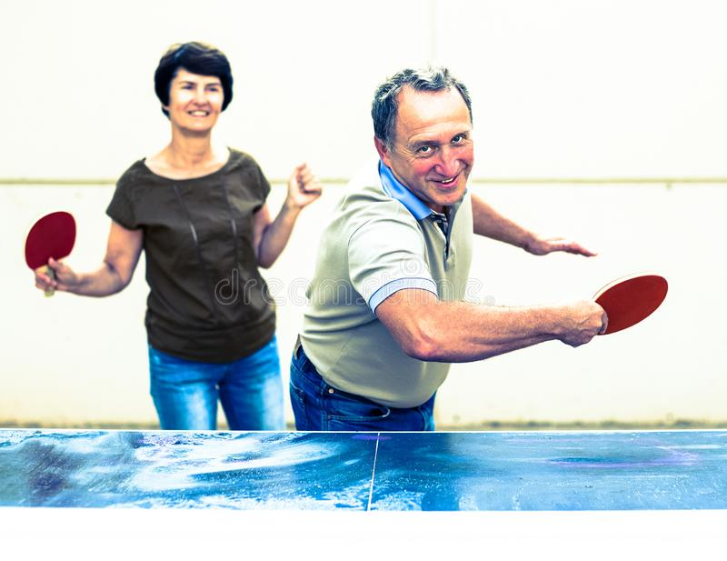 Mature man and woman playing table tennis. Happy mature men and women playing table tennis royalty free stock photos