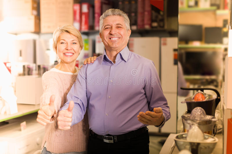 happy mature married couple in shopping center buys small kitchen household appliances royalty free stock images