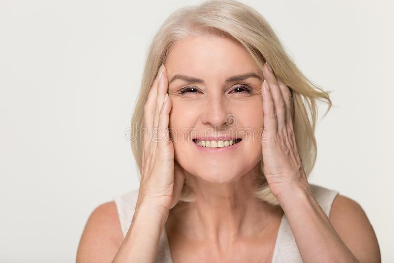 Happy mature woman touching face isolated, anti aging beauty concept royalty free stock photo