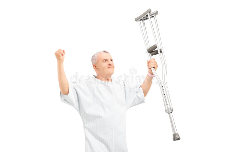 A happy mature patient holding crutches and gesturing happiness stock image