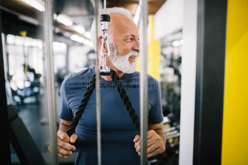 Happy senior people doing exercises in gym to stay fit royalty free stock photo
