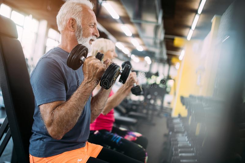 Happy senior people doing exercises in gym to stay fit royalty free stock images