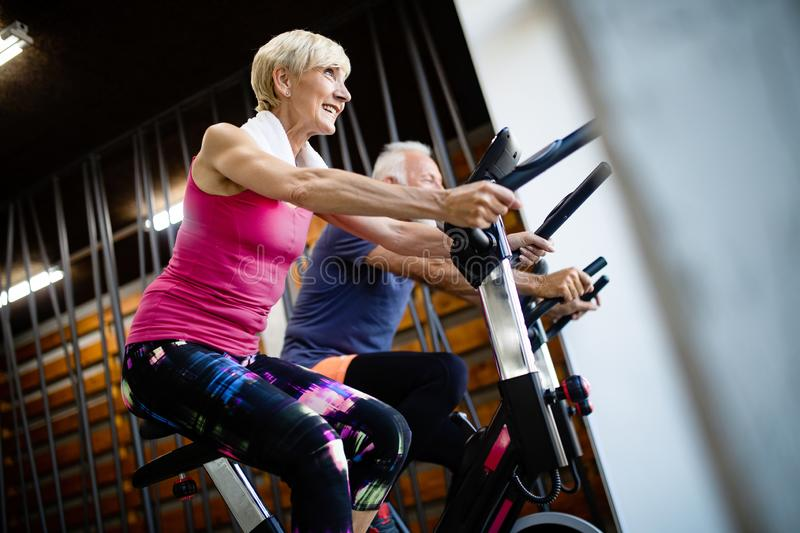 Happy senior people doing indoor biking in a fitness club royalty free stock images