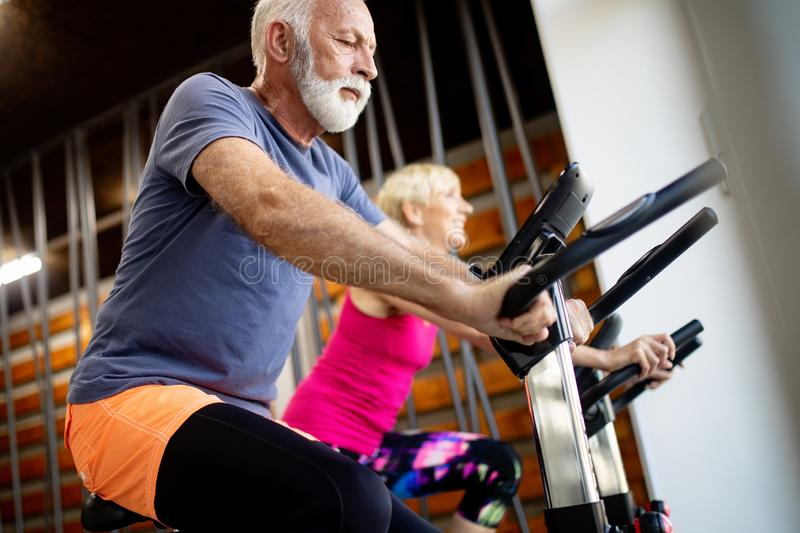 Happy senior people doing indoor biking in a fitness club royalty free stock photography
