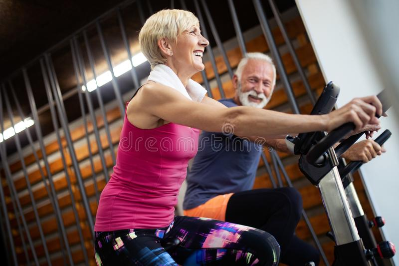 Happy senior people doing indoor biking in a fitness club royalty free stock image