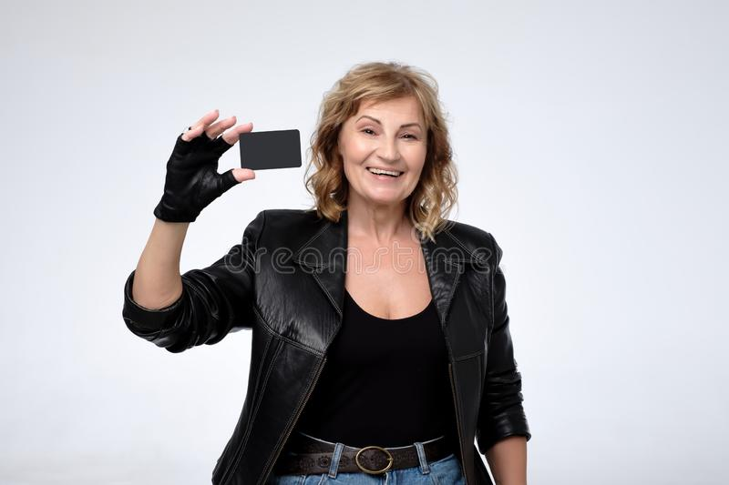 Happy blond woman showing blank credit card. Focus on card. stock photos