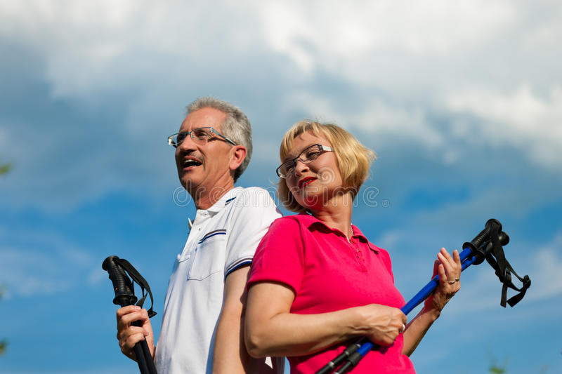 Happy mature or senior couple doing Nordic walking royalty free stock images