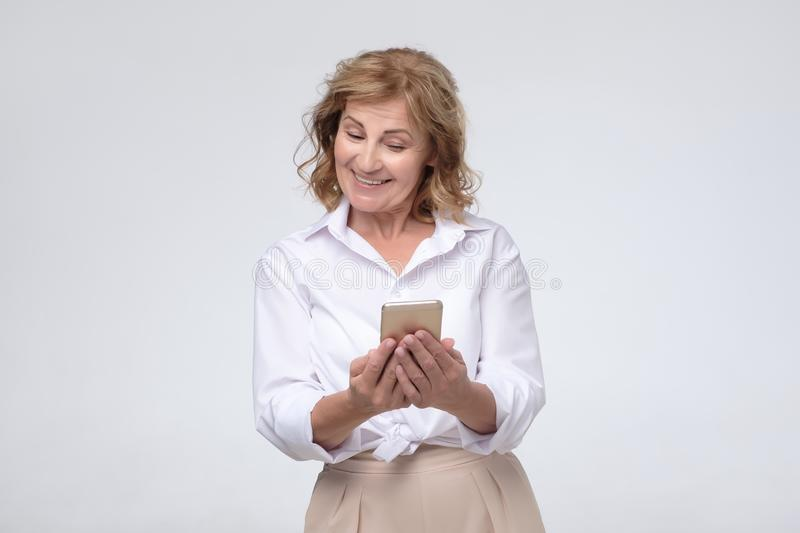 Happy mature senior woman holding smartphone using mobile online apps stock photography