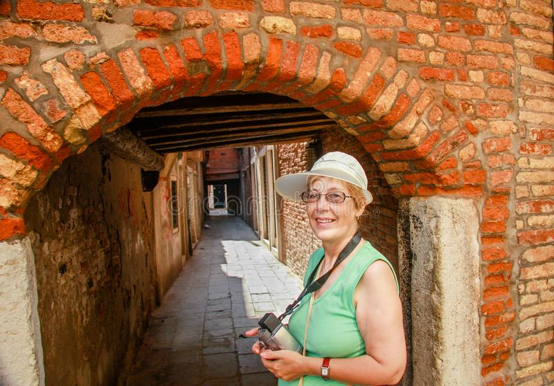 Happy mature tourist woman stays against narrow street in Venice. Happy mature tourist woman travelling in Italy stays against narrow street and arch in Venice stock images