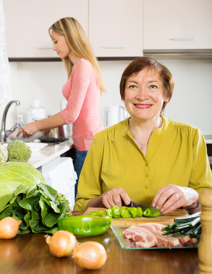 Happy mature woman with adult daughter cooking together royalty free stock images