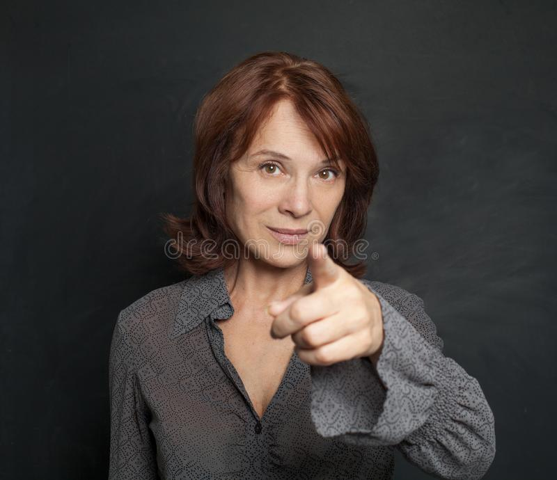 Happy mature woman businesswoman pointing on blackboard royalty free stock photo