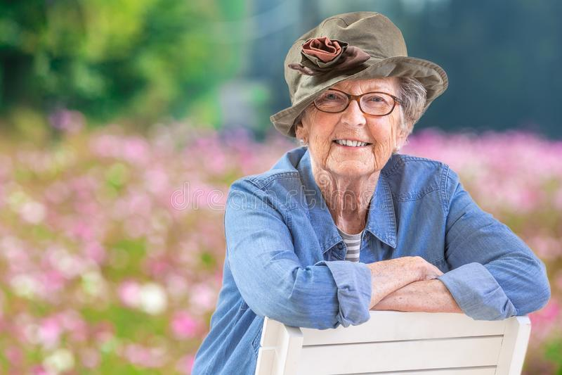 Happy mature woman with casual wear and a hat in front of a pink cosmos flower field stock images