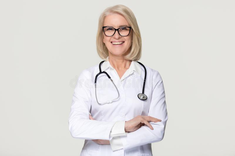Happy mature woman doctor portrait isolated on grey background stock images