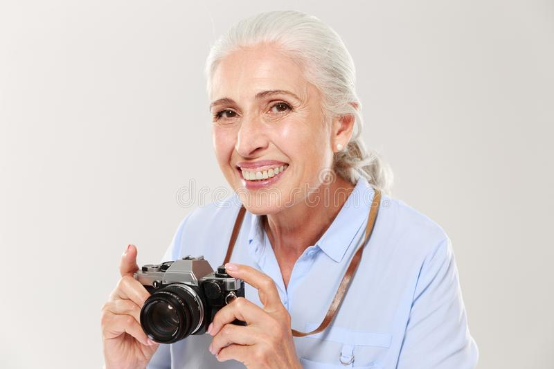 Happy mature woman holding retro camera isolated over white stock photos