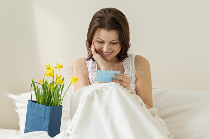 Happy mature woman at home in bed enjoying the gift of flowers and reading greeting card with smile. Emotion of happiness, joy, stock image