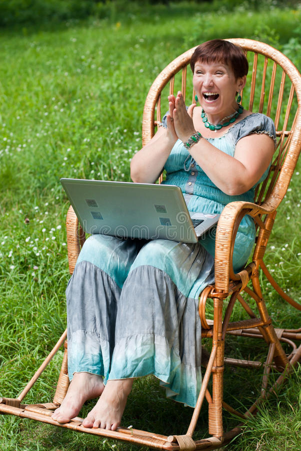 Download Happy Mature Woman With Laptop In Rocking Chair Stock Images - Image: 20529744