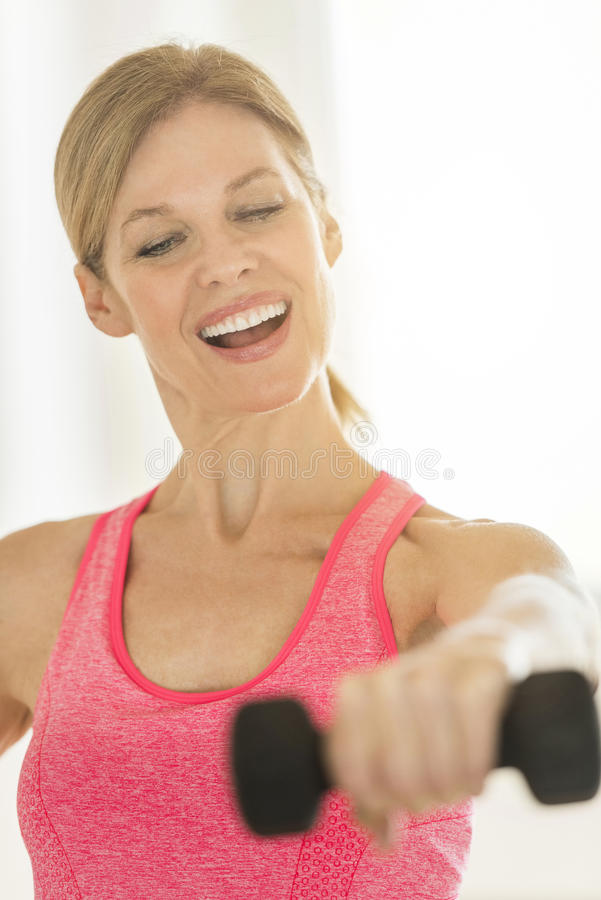 Happy Mature Woman Lifting Dumbbell At Home royalty free stock images