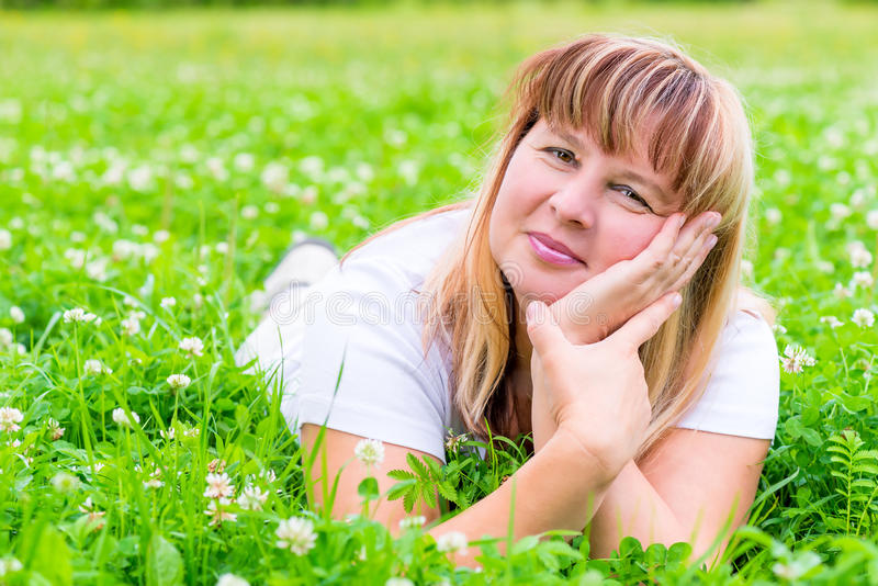 Happy mature woman lying on a meadow royalty free stock images