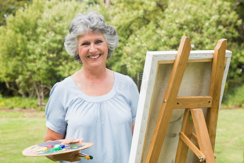 Happy mature woman painting on canvas stock photos