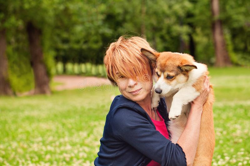 Happy mature woman with puppy dog pet in summer park stock photography