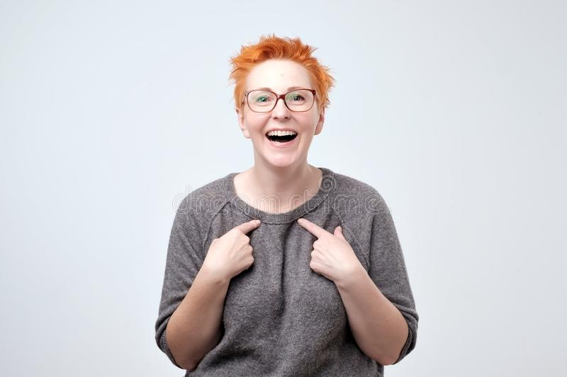 Happy mature woman with red hair pointing fingers at herself. Select me please concept. She can not believe in her luck royalty free stock photo