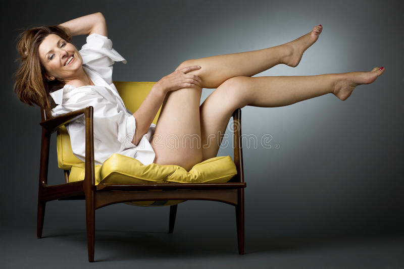 Happy mature woman relaxing on chair. stock images