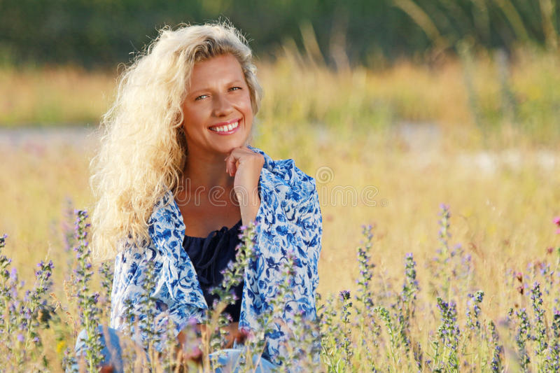Happy mature woman relaxing in the meadow stock photos