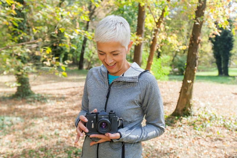 Happy Mature Woman With Retro Camera royalty free stock image