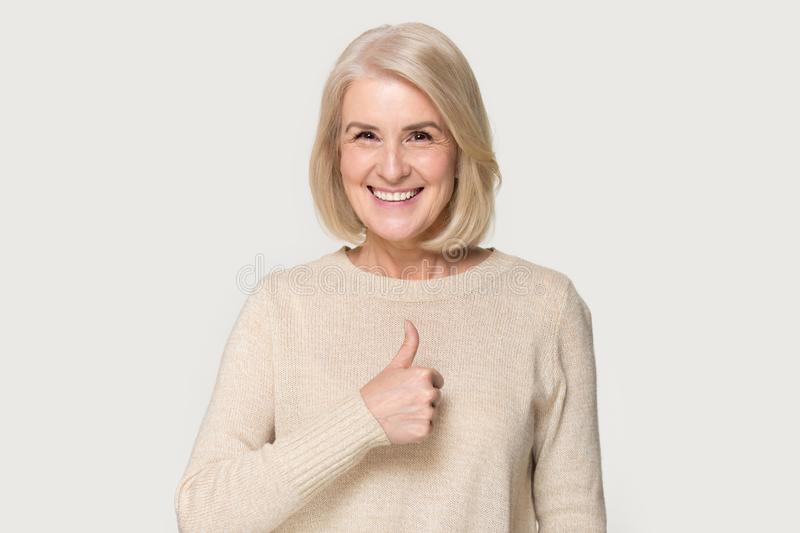 Happy mature woman show thumbs up recommending service stock images