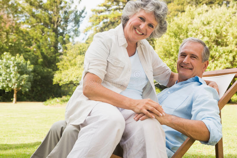 Happy mature woman sitting on her husband on deck chair royalty free stock image