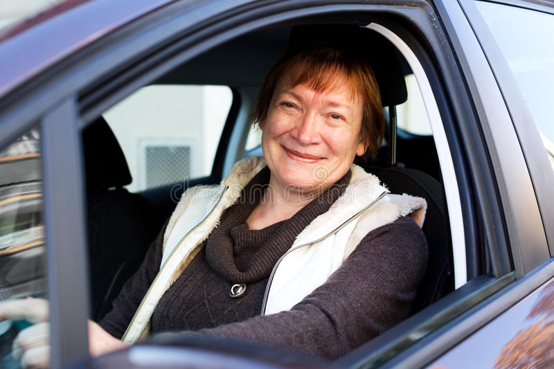 Happy mature woman sitting in new car stock images