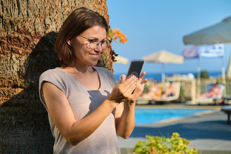 Happy mature woman with smartphone. Female resting in resort spa hotel stock photo