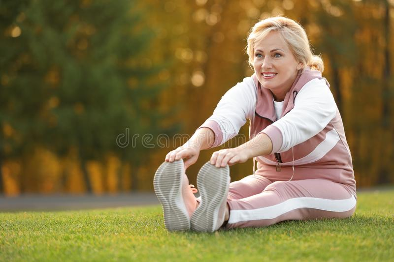 Happy mature woman stretching. Active lifestyle. Happy mature woman stretching in park. Active lifestyle stock images