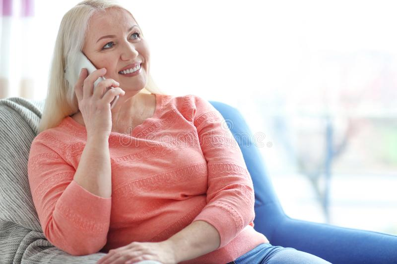 Happy mature woman talking on phone while sitting in armchair stock images