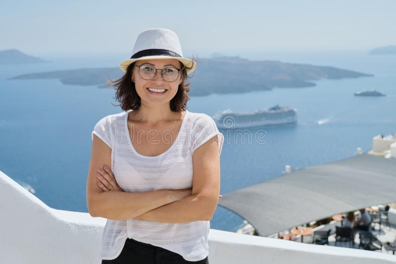 Happy mature woman tourist traveling on famous island Santorini royalty free stock images