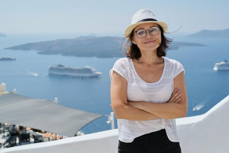 Happy mature woman tourist traveling on famous island Santorini stock photography