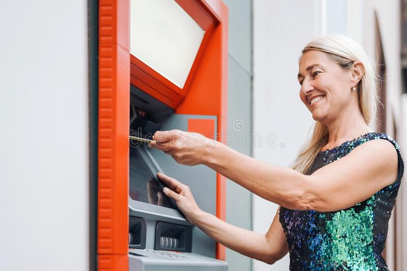 Happy mature woman withdraw money from bank cash machine with debit card - Senior female doing payment with credit card in ATM stock photo