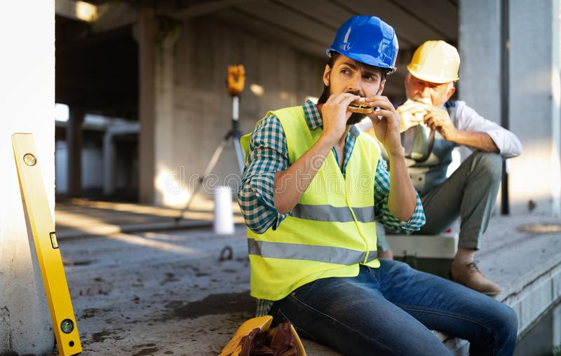 Happy mature and young engineer, architect, worker sitting at building site and resting stock image