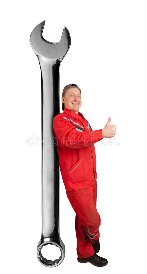 Happy mechanic with big spanner. Showing ok gesture royalty free stock photography