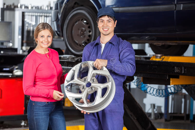 Happy Mechanic And Customer With Hubcap. Portrait of happy mechanic and female customer with hubcap at garage royalty free stock images