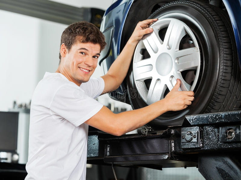 Happy Mechanic Fixing Hubcap To Car Tire. Side view portrait of happy male mechanic fixing hubcap to car tire at garage royalty free stock photo