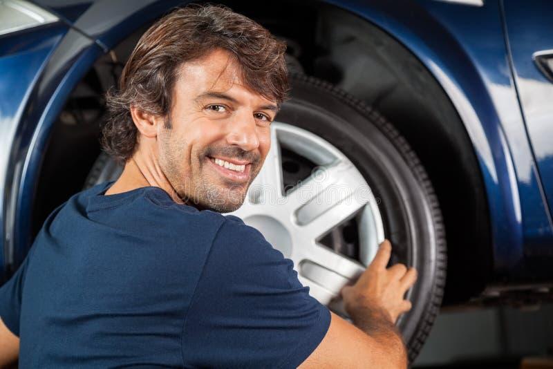 Happy Mechanic Fixing Hubcap To Tire. Portrait of happy mechanic fixing hubcap to car tire at garage royalty free stock photos