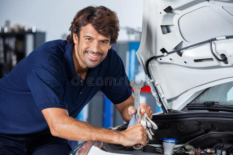 Happy mechanic leaning on car with open hood stock image for Garage happy car