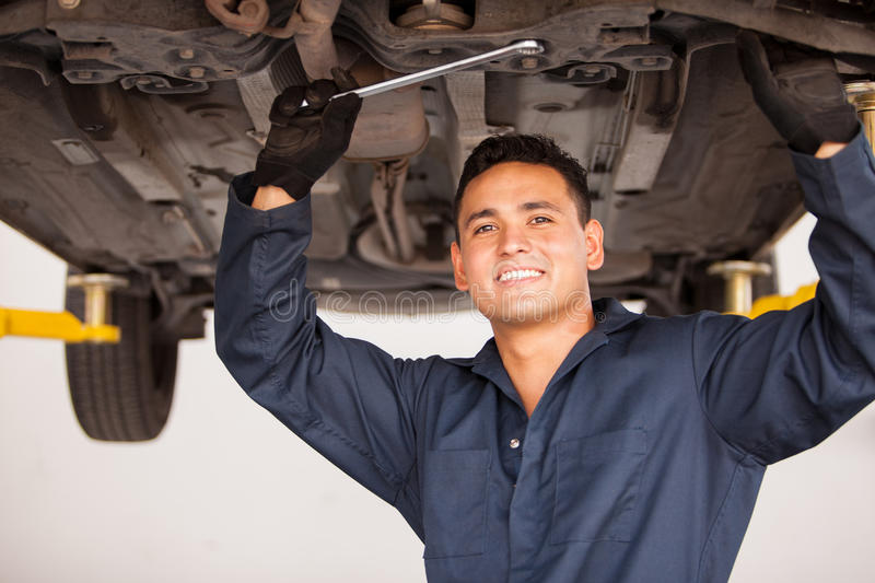 Happy mechanic working on a car. Portrait of a handsome young mechanic working on a suspended car at an auto shop and smiling royalty free stock photography