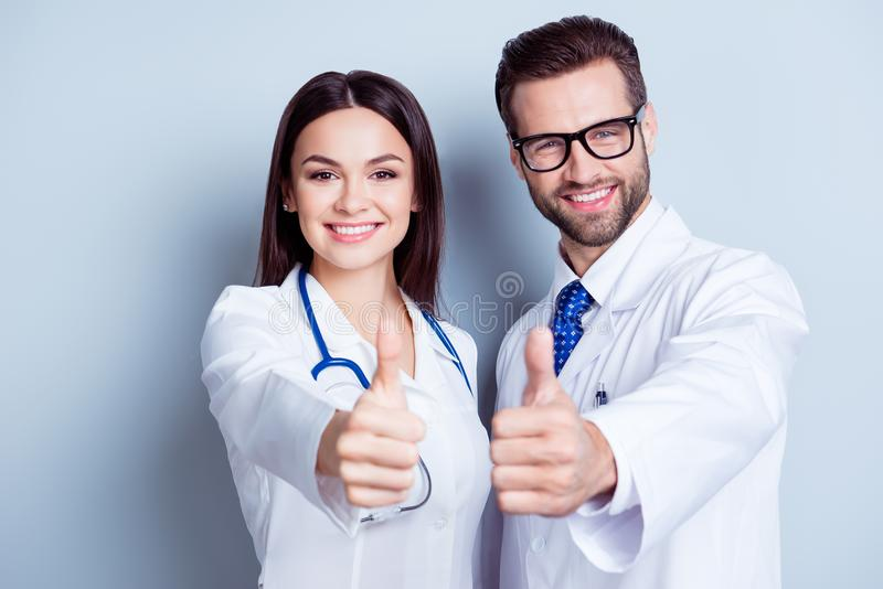 Happy medic workers. Portrait of two doctors in white coats and. Glasses showing thumb-up against white background stock photos