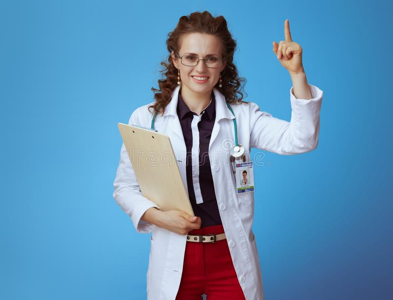 Happy medical doctor woman with clipboard rising finger on blue. Happy elegant medical doctor woman in bue shirt, red pants and white medical robe with clipboard stock photos