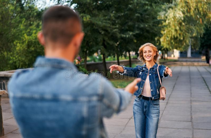 Happy meeting of two lovers hugging in the street. Young women greeting her boyfriend embracing each other. Love and dating concept royalty free stock photos