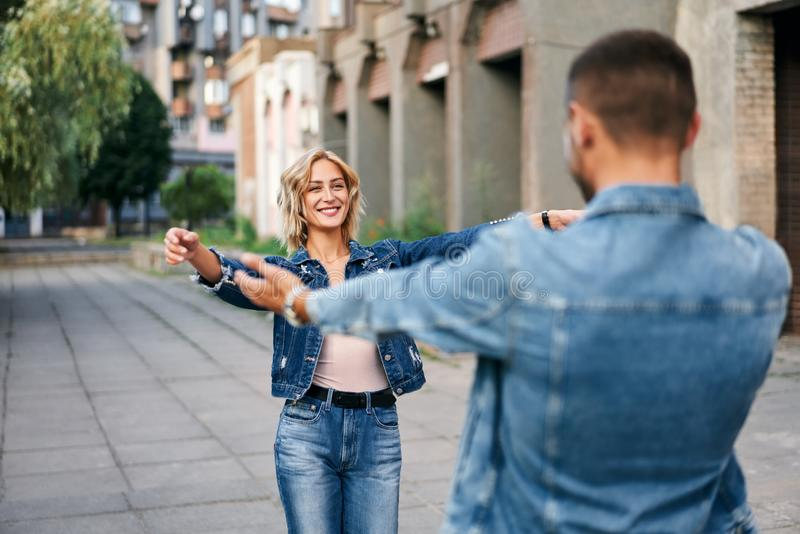 Happy meeting of two lovers hugging in the street. Young women greeting her boyfriend embracing each other. Love and dating concept stock images