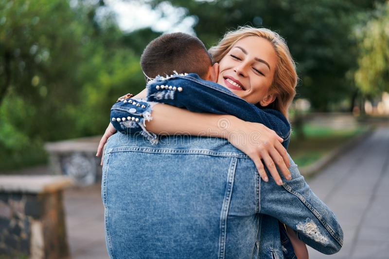 Happy meeting of two lovers hugging in the street. Young women greeting her boyfriend embracing each other. Love and dating concept royalty free stock image