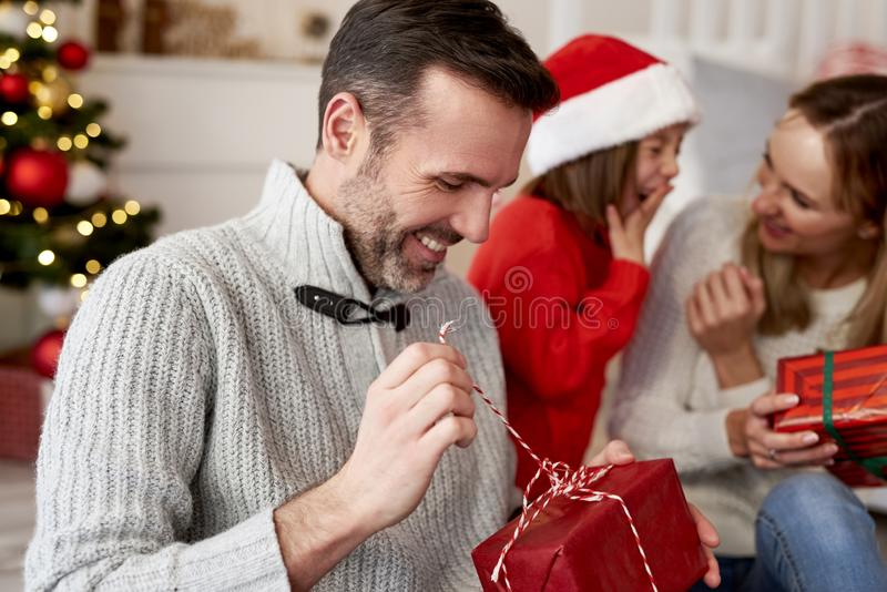 Happy man opening Christmas present royalty free stock photography